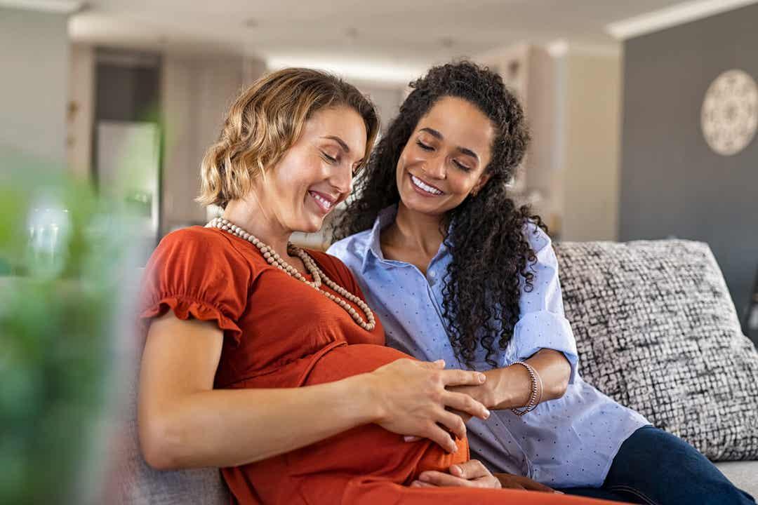 En kvinde, der rører ved sin partners gravide mave