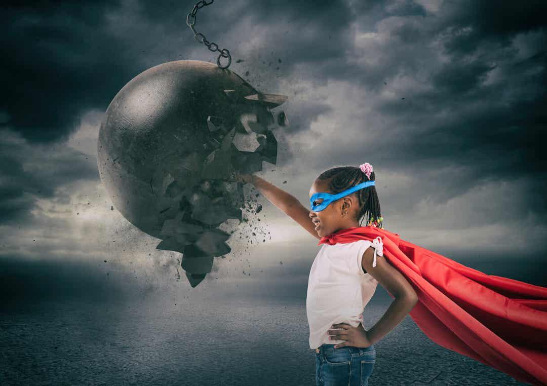 Een klein meisje dat een cape en masker draagt en met haar vuist een brekende bal verplettert.