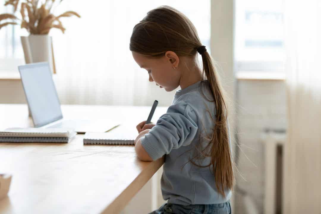 Een kind zit aan een tafel met rechte rug.