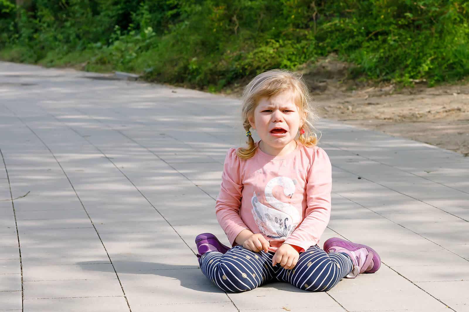A toddler girl having a tantrum on the sidewalk.