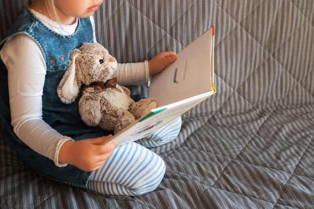 Et lille barn, der læser for at fejre den internationale dag for børnebøger