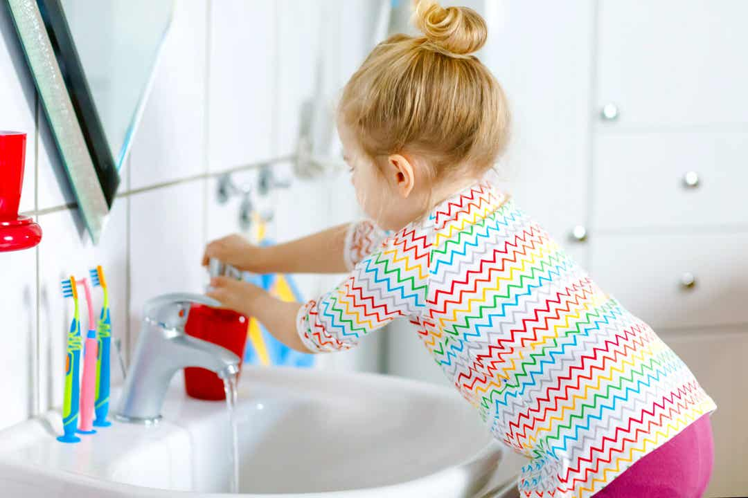 A 3-year-old girl washing her hands in the bathroom sink.