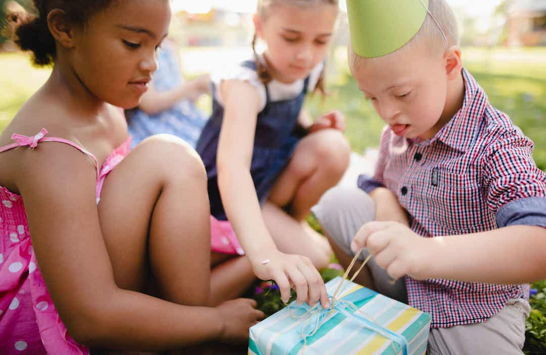 A boy with down syndrome and two other young girls opening a present.