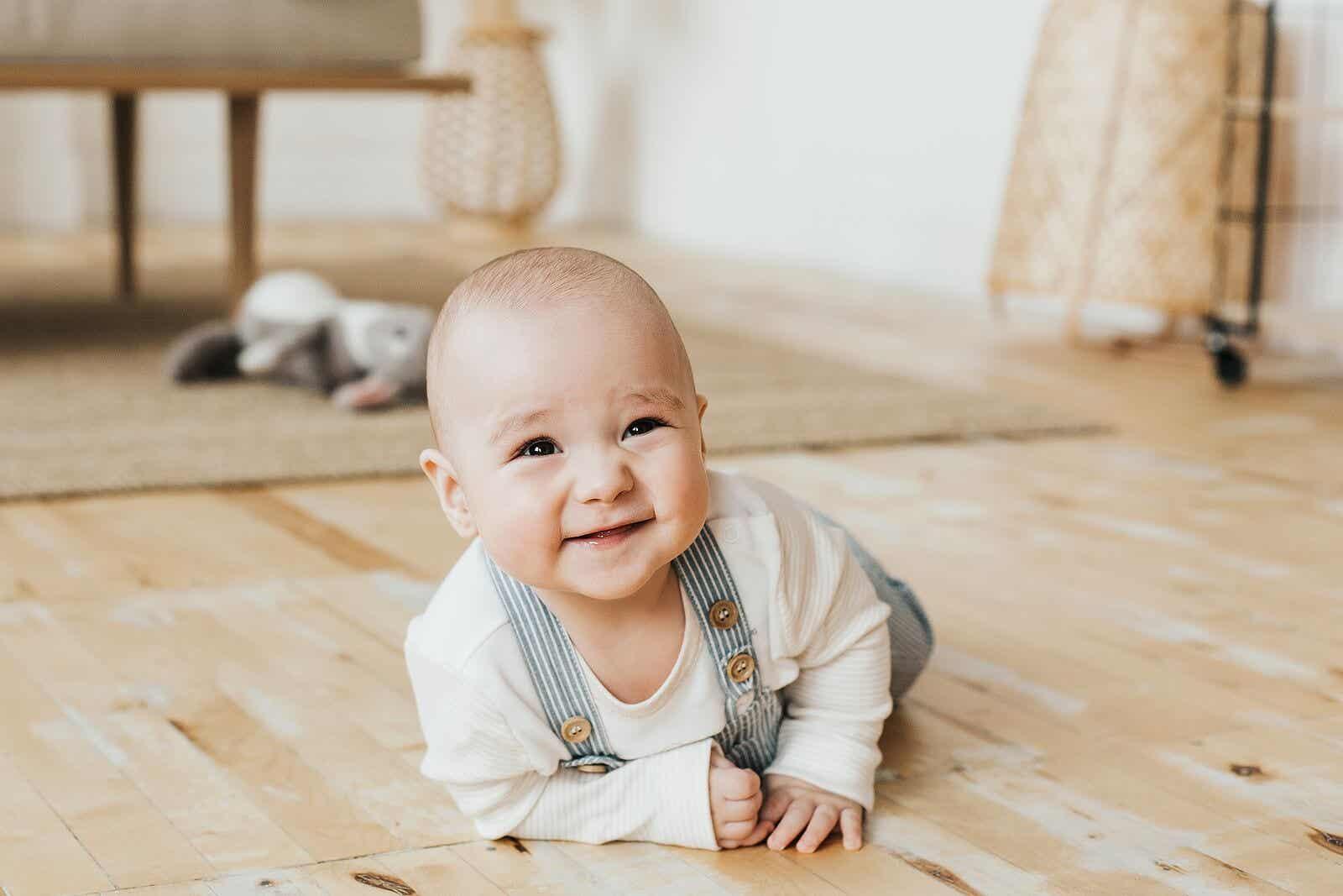 Een lachende baby liggend op zijn buik met zijn hoofd omhoog.