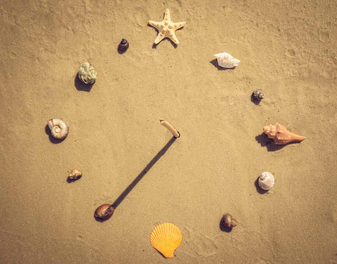 Een zelfgemaakte zonnewijzer met schelpen en een stok in het zand.
