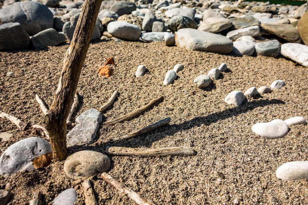 Een zonnewijzer gemaakt van rotsen en stokken op het strand.