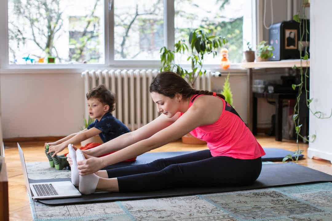 Een moeder en haar jonge kind doen teenaanrakingen terwijl ze een oefeningsroutine op de computer volgen.