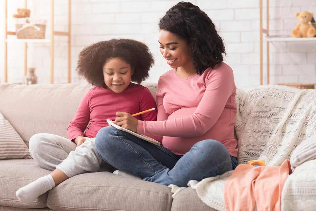 En gravid kvinde sidder med sin unge datter og vælger navne