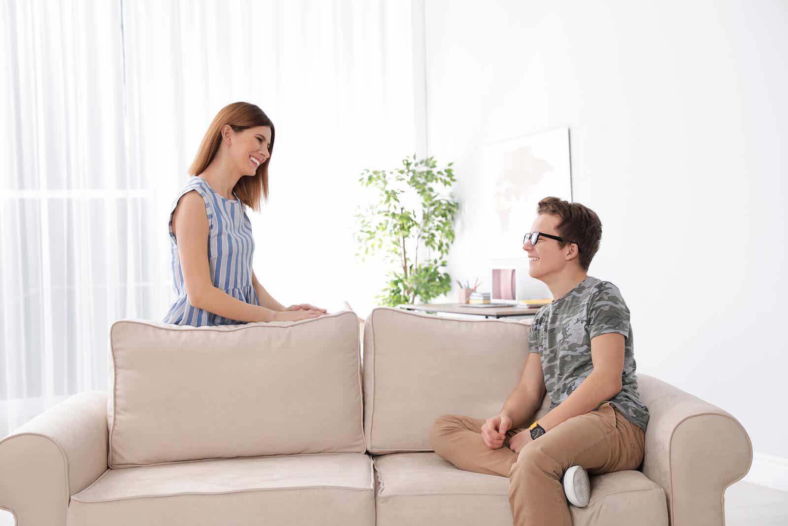 Een moeder en haar tienerzoon praten en glimlachen naar elkaar.