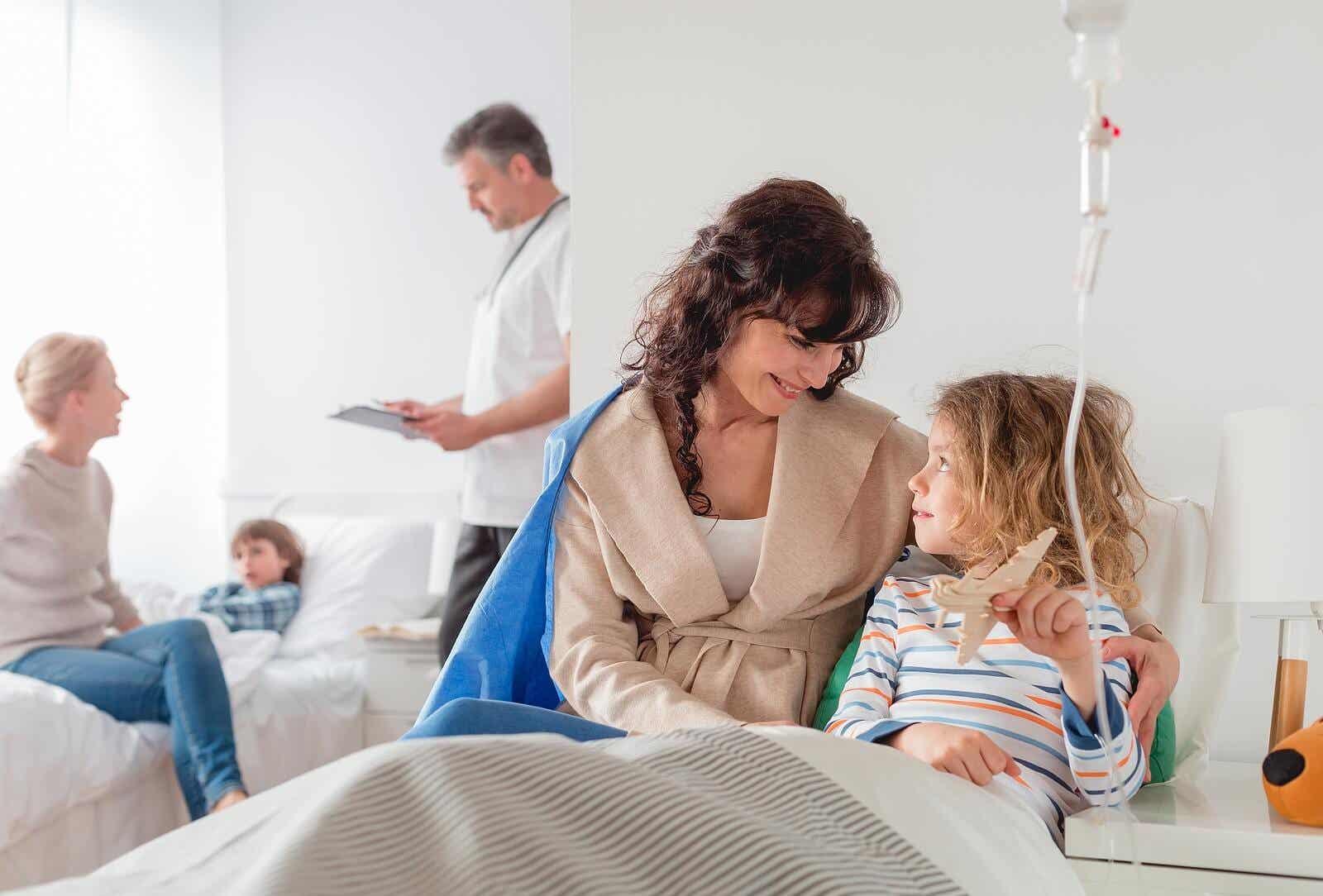 Młoda dziewczynka w szpitalnym łóżku, podłączona do kroplówki, rozmawiająca z mamą.