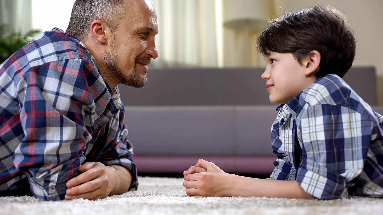 A father and son lying on the floor looking into one another's eyes.