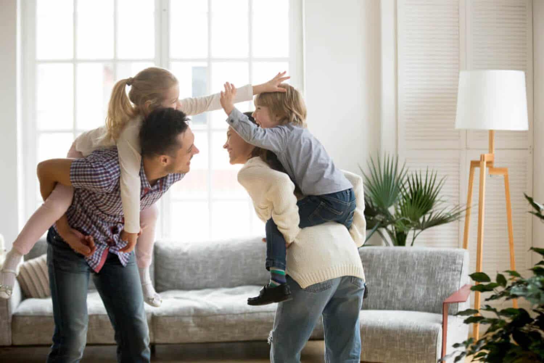 Föräldrar som leker med sina barn i sitt vardagsrum.