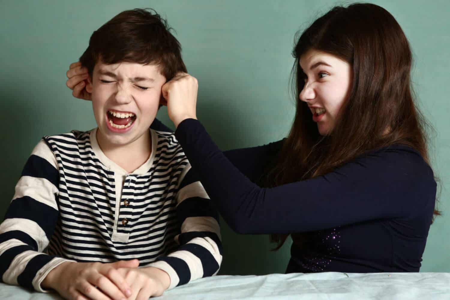 A girl pulling on her brother's ears.