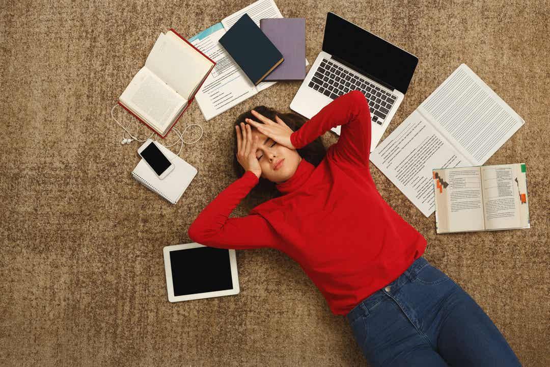 Een jongere die op de grond ligt en zich overweldigd voelt door schoolwerk.