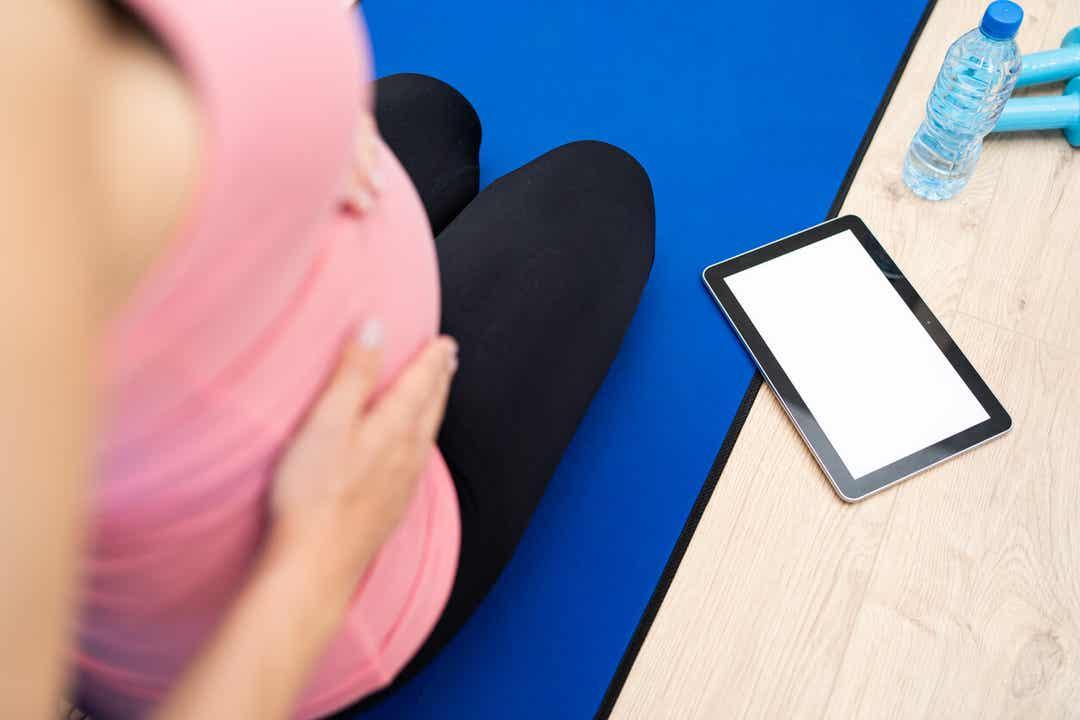 Een zwangere vrouw die traint en naar haar tablet kijkt.