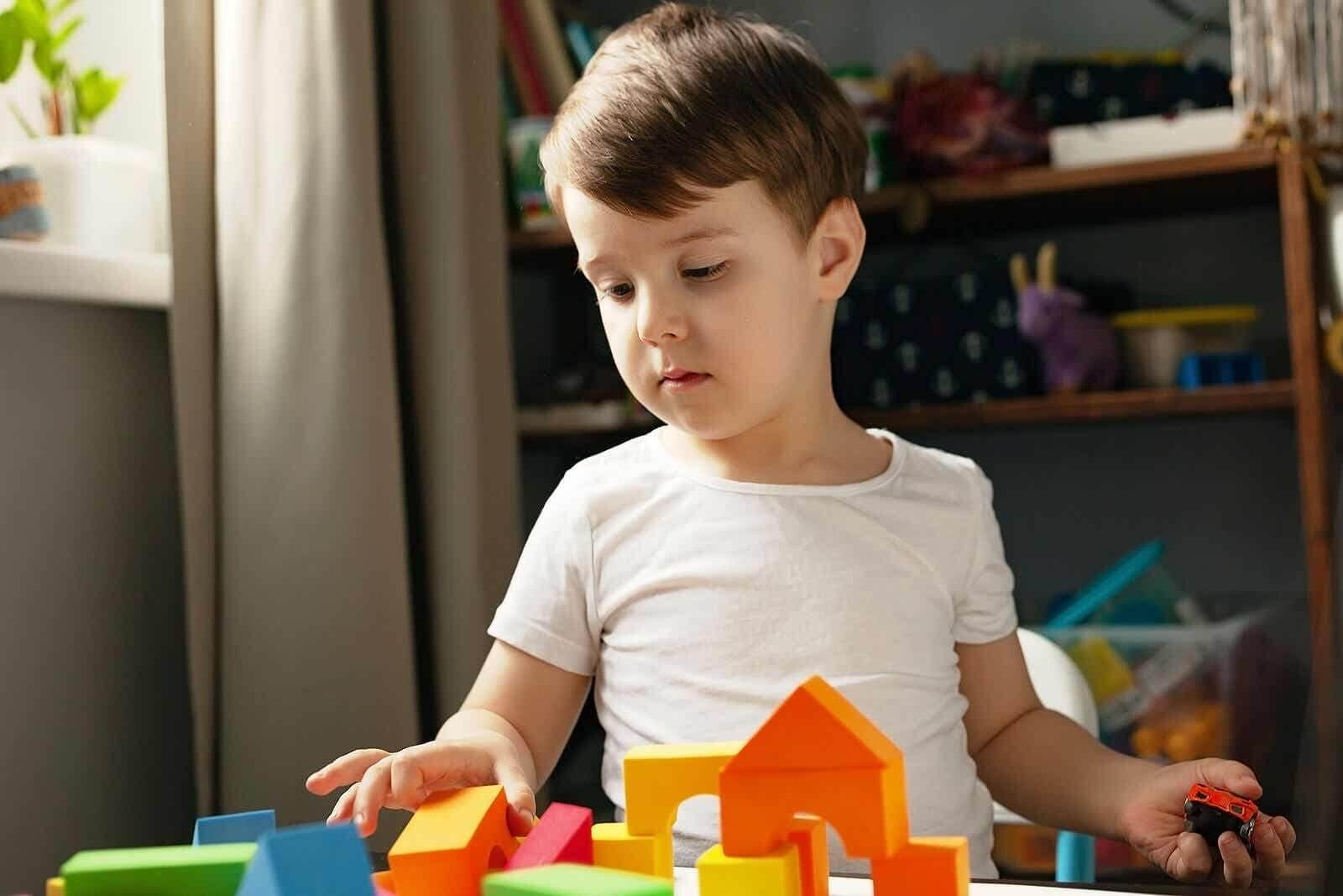 Child playing with building blocks, but not wanting to pick them up.
