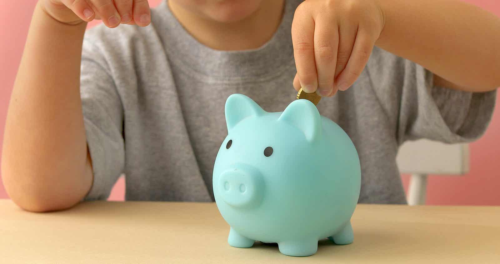 Child putting money into a piggy bank.