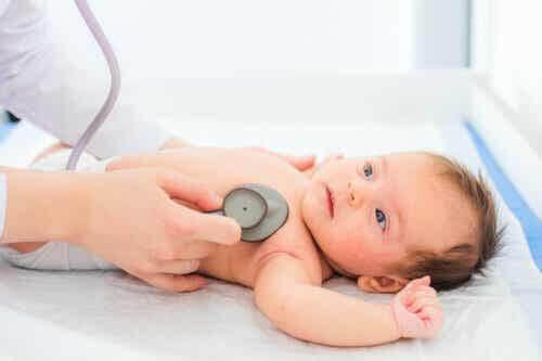 Herzgeräusche - Kinderarzt hört das Herz eines Babys ab.