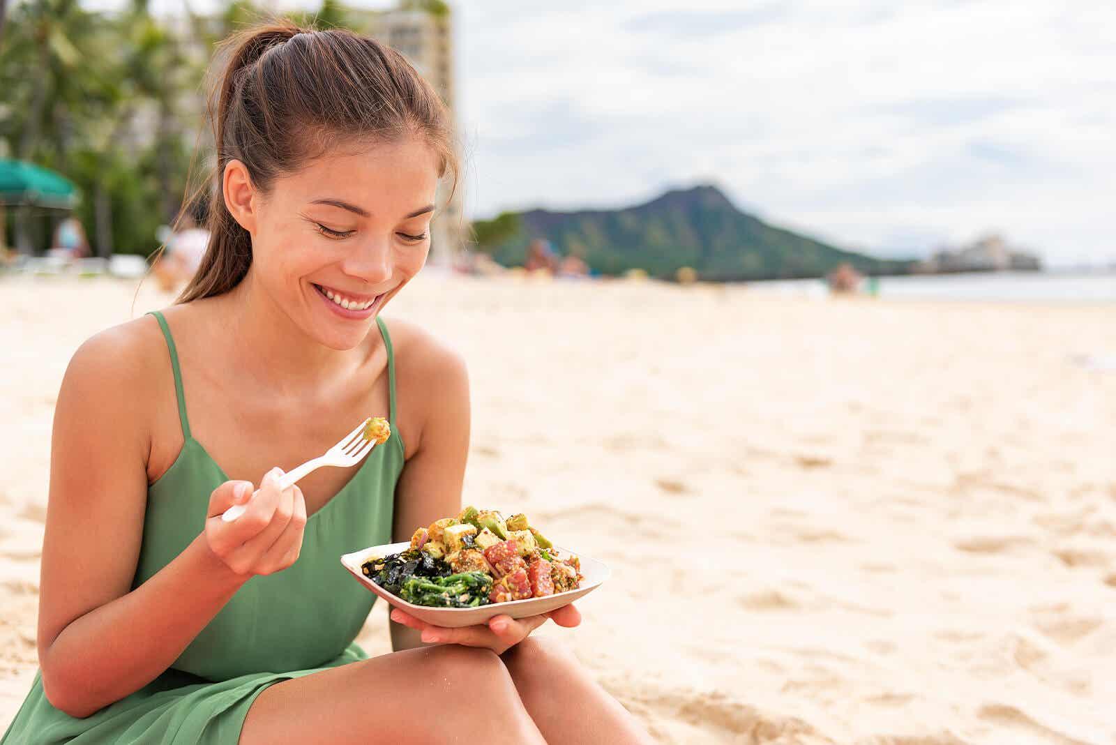 Vrouw die op het strand gezond voedsel eet dat thuis wordt bereid om voedselvergiftiging te voorkomen.