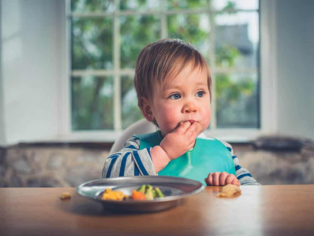 En baby spiser med hænderne