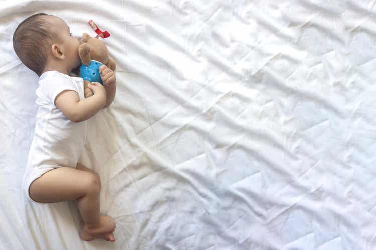 A baby sleeping with a stuffed animal.