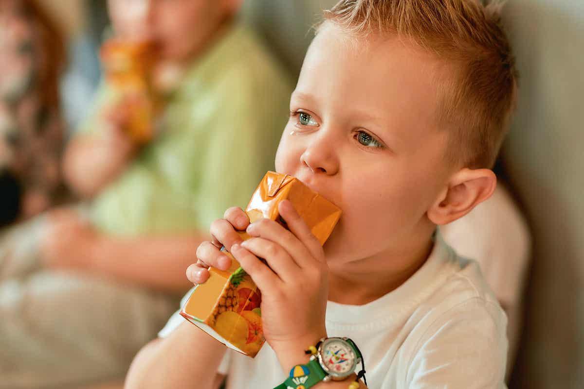 Chłopiec pijący sok z pudełka.
