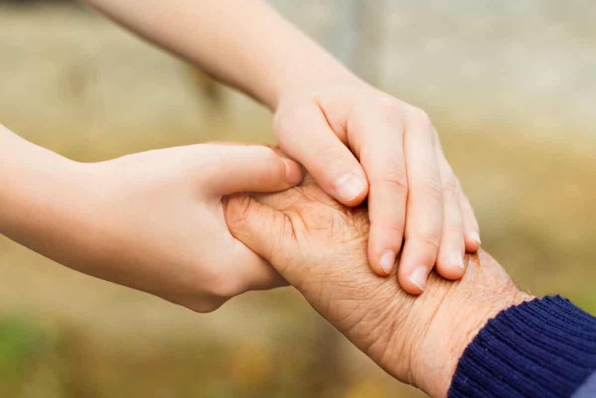 Et barn som holder hendene med en eldre person.