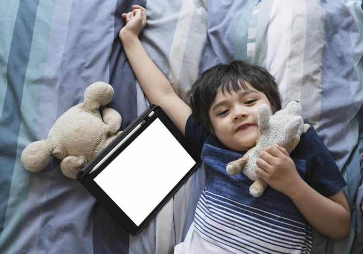 A child laying down next to a tablet.