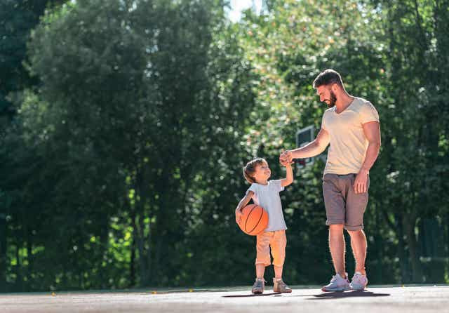 Een vader die basketbal speelt met zijn kind.