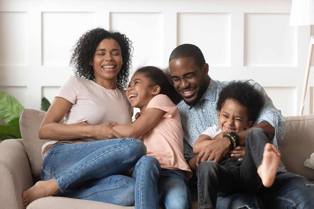 En familj som skrattar tillsammans i soffan.