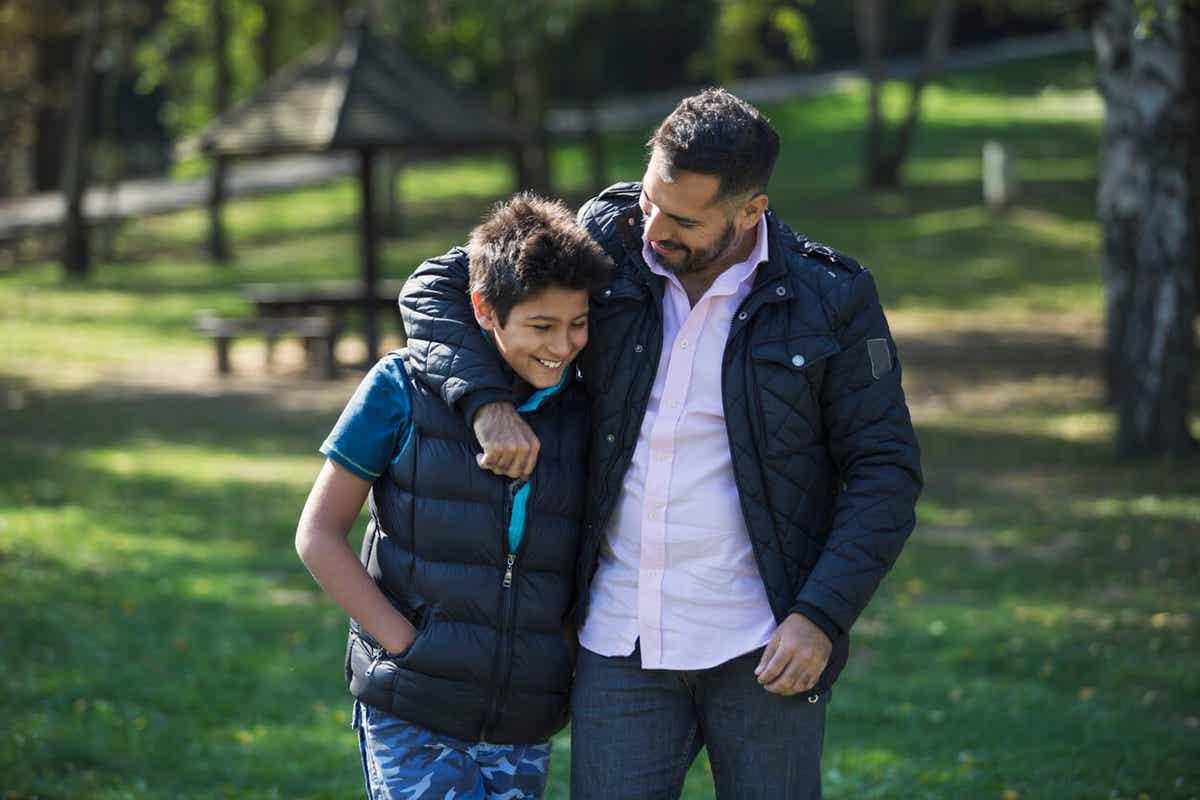 En far og søn, der går gennem parken, mens faren hjælper sønnen med at øge selvtilliden