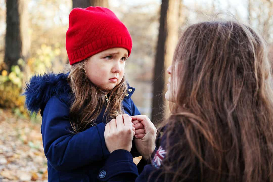 En mor, der krummer sig ned for at tale med sin lille datter, der ser ked ud