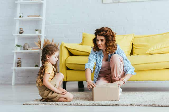 A mom opening a box with her daughter.