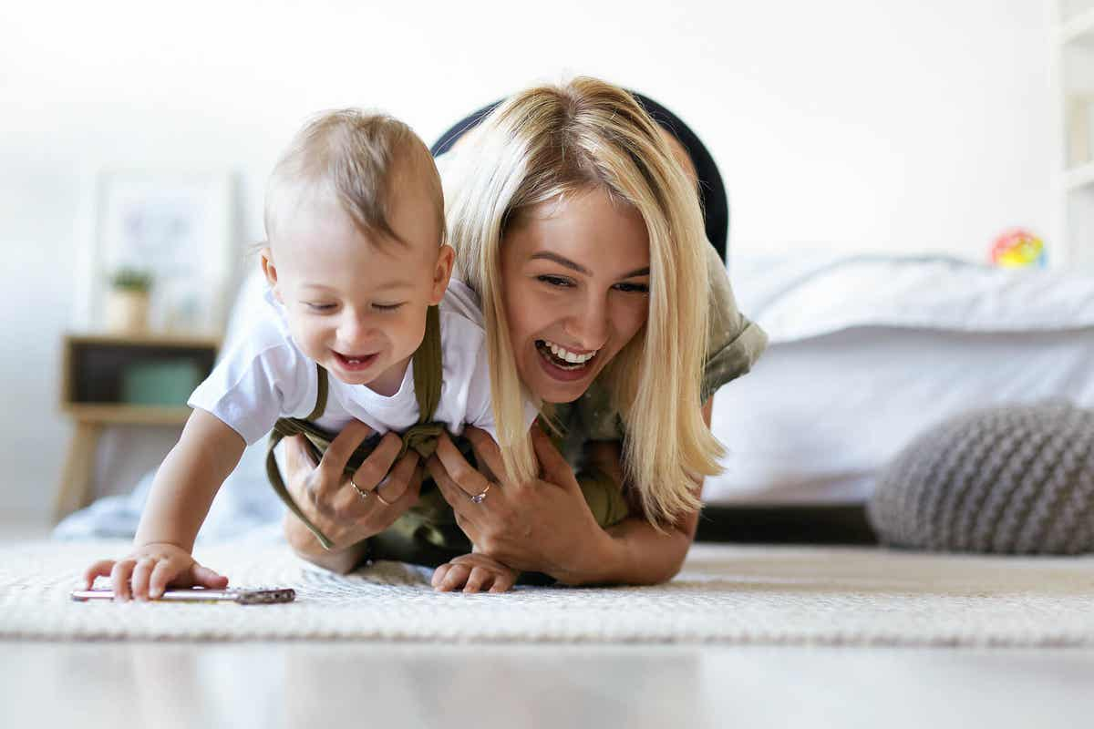 A mom playing with her baby on the bed.