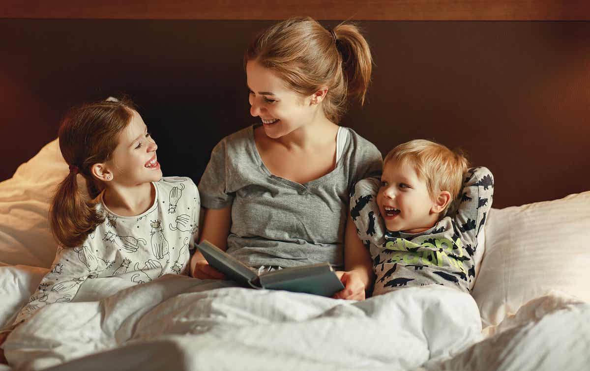 En mor læser med sine børn i sengen