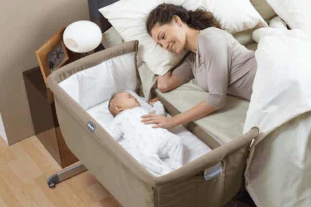 En kvinna som sover tillsammans med sin bebis.
