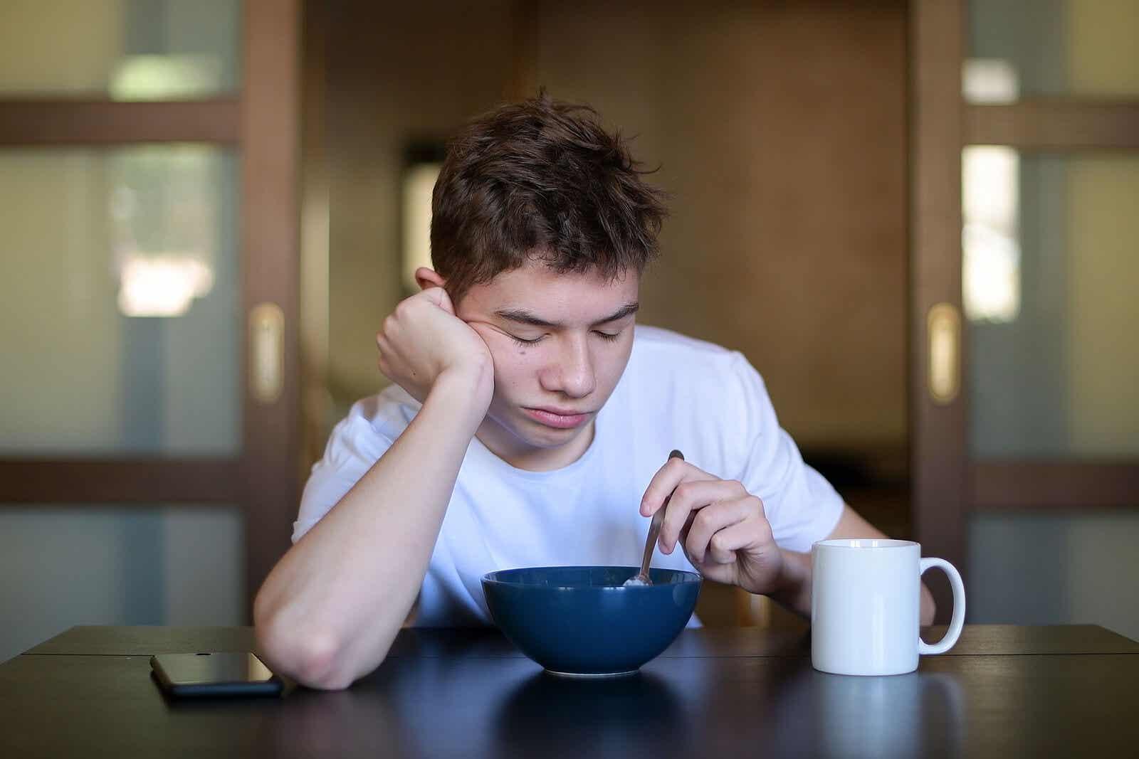 En teenager, der er træt ved morgenmaden