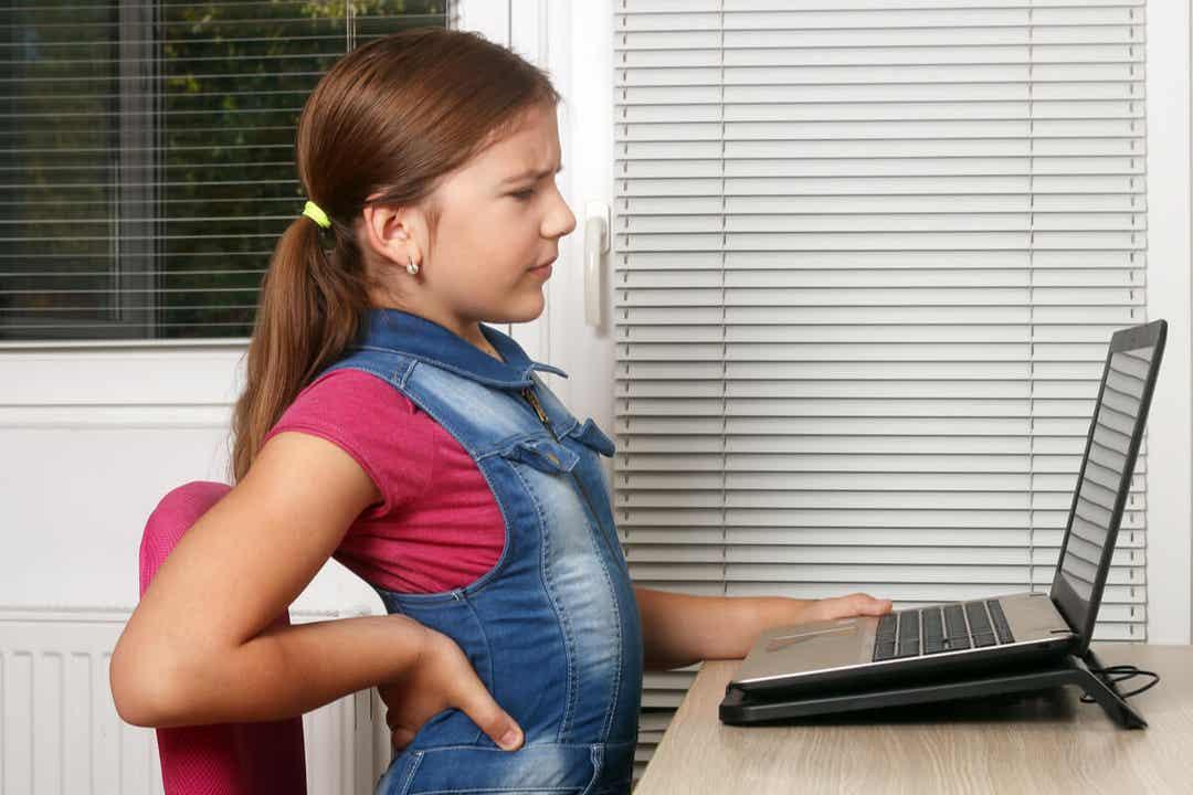 En ung pige, der sidder ved et skrivebord, har rygsmerter
