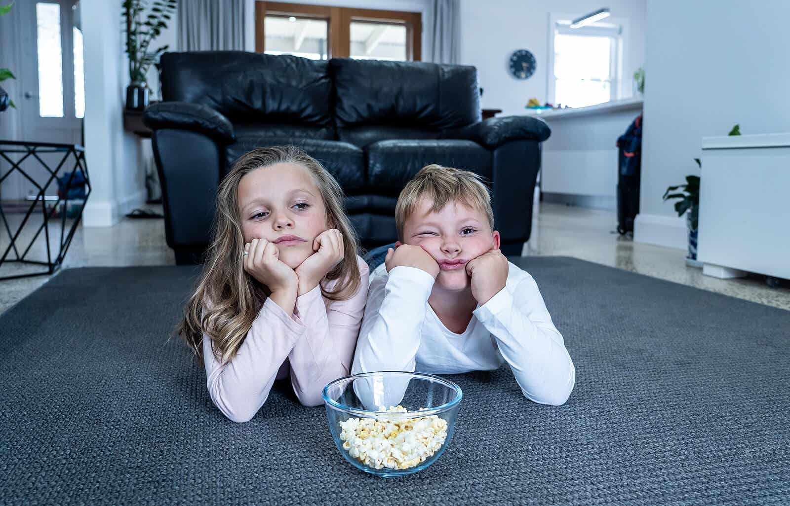 Two bored children eating popcorn in front of the TV.