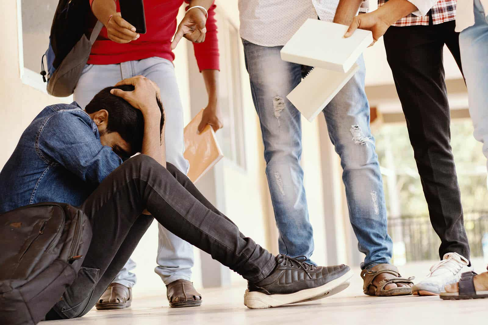 A teenage boy sitting on the floor at school, surrounded by a group of bullies.
