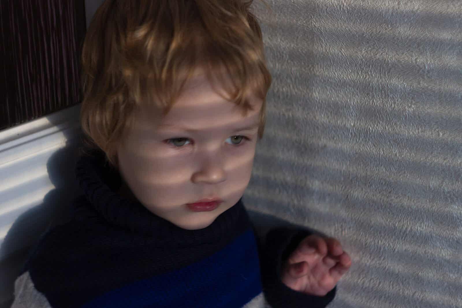 A sensitive toddler boy sitting in a corner.