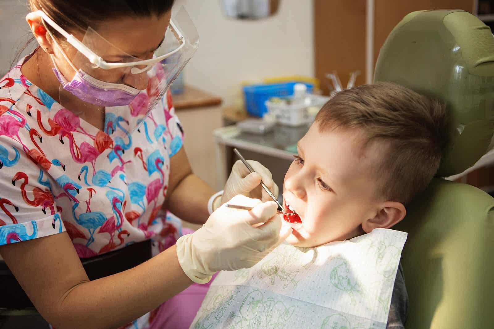 En kvindelig tandlæge, der behandler en ung dreng