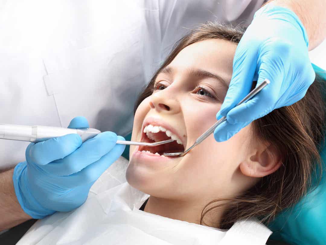 En tandlæge behandler en ung pige