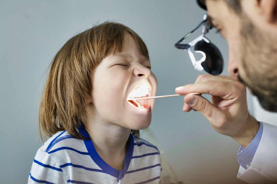 En børnelæge, der tjekker et barns hals