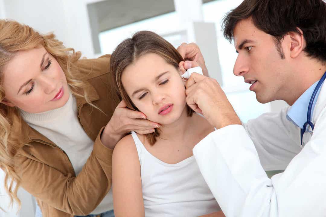 En børnelæge ser på et barns øre