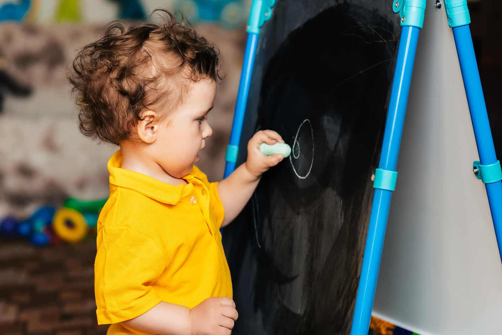 A toddler scribbling on a chalkboard.