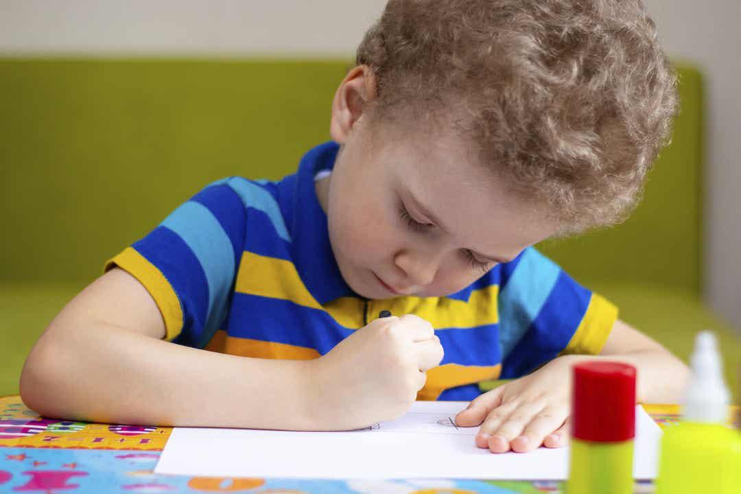 A little boy making a drawing.