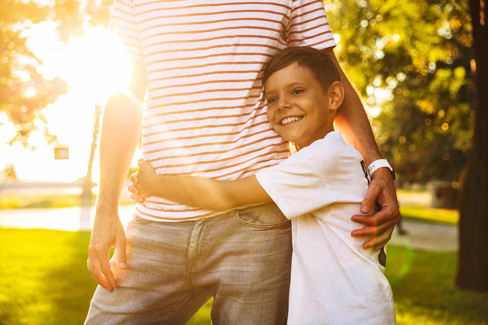 Een gelukkige en zelfverzekerde jongen die de taille van zijn vader omhelst.
