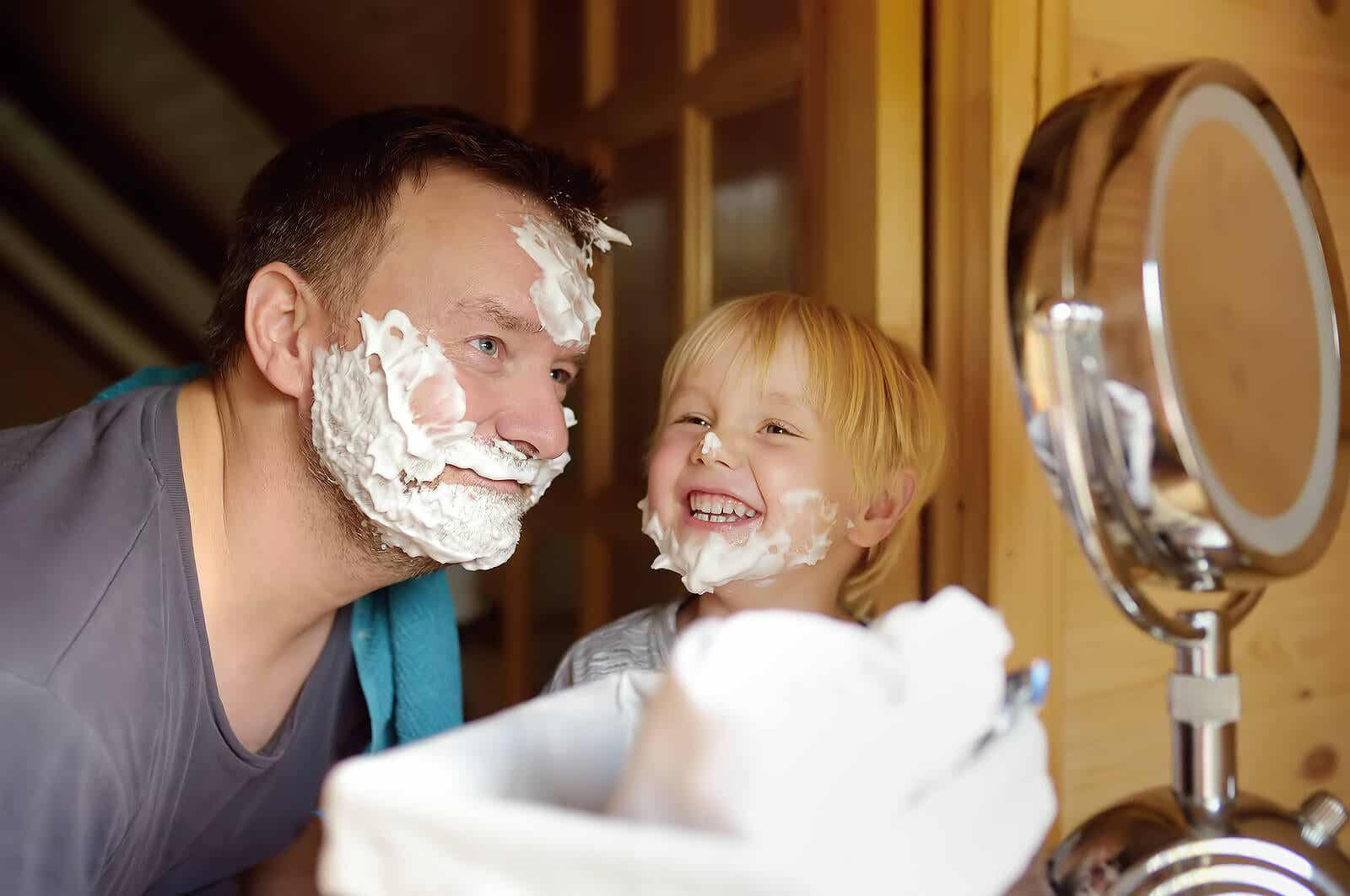 A father and son with shaving cream on their faces, smiling.