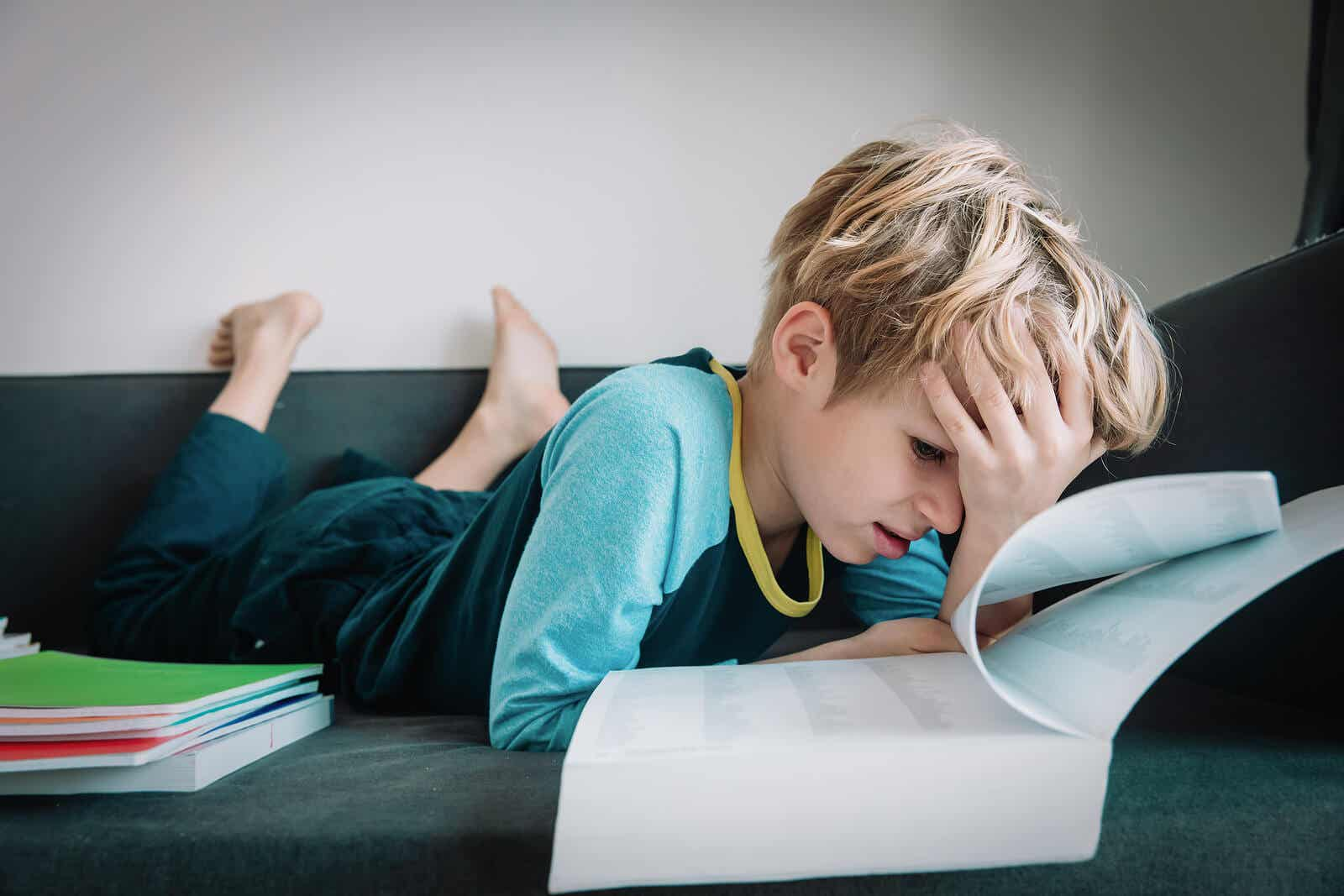 A child looking at a school book while with his head on his forehead, looking frustrated.